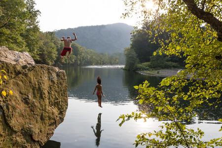 Young couple jumping from rock ledge,Hamburg,Pennsylvania,USA