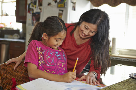 leading education: Mother guiding daughter in homework
