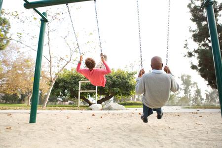 65 70 years: Senior couple on swings in park