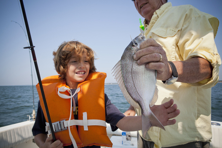proudly: Boy and grandfather with caught fish on boat,  Falmouth, Massachusetts, USA
