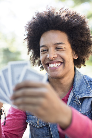 cropped out: Young man playing cards LANG_EVOIMAGES