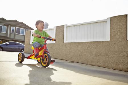 shadowed: Boy cycling on driveway