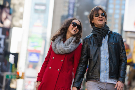 retail scene: Young tourist couple holding hands, New York City, USA