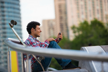 Man smiling at text message on mobile phone