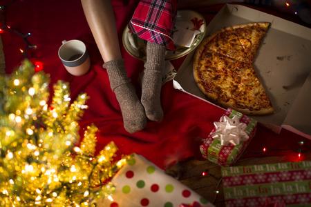 Piernas de la mujer joven entre regalos de Navidad y caja de pizza