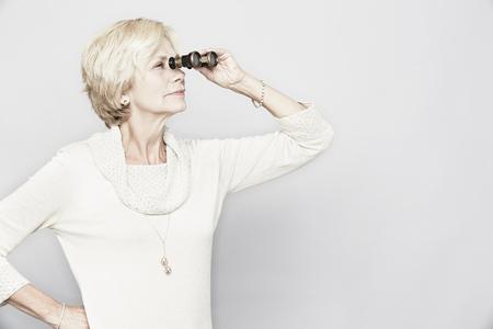 60 64 years: Studio portrait of senior woman looking through binoculars LANG_EVOIMAGES