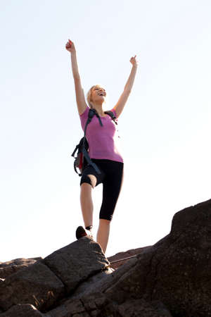 getting out: Woman standing at the top of Mont St-Hilaire with arms raised