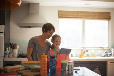 worktops: Mother and daughter looking at digital tablet in kitchen