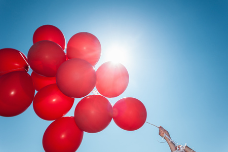 bunched: Hands holding bunch of red balloons against blue sky