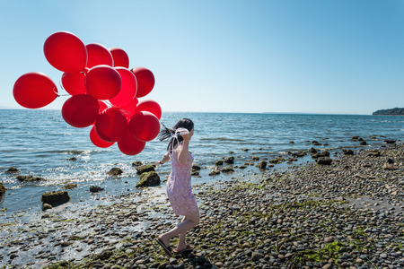 Mature woman pulling bunch of balloons LANG_EVOIMAGES