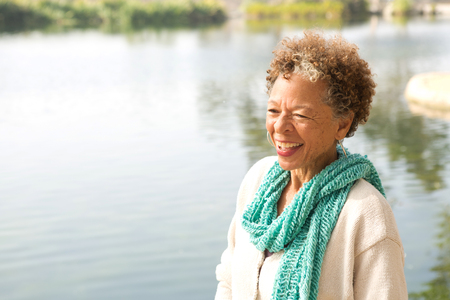 65 69 years: Portrait of senior woman by lake in park