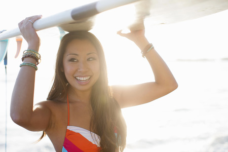Young woman carrying surfboard,San Diego,California,USA