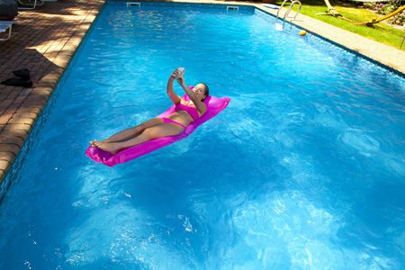 Girl on inflatable bed in pool