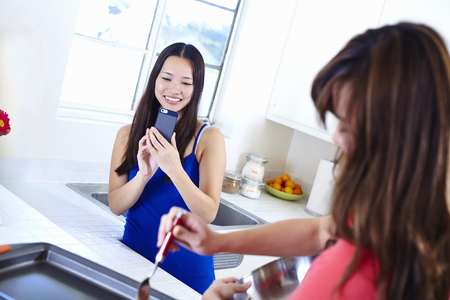 worktops: Two young women in kitchen taking photograph with mobile phone