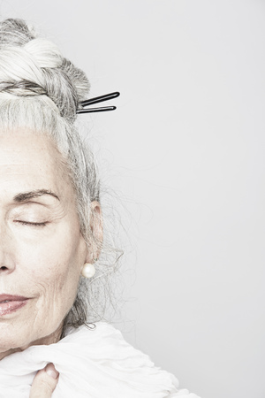 60 65 years: Cropped studio portrait of senior woman with eyes closed LANG_EVOIMAGES