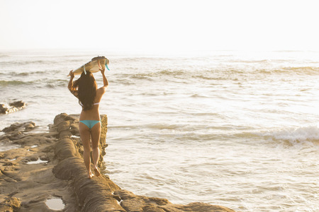 above 18: Young woman holding up surfboard,San Diego,California,USA LANG_EVOIMAGES