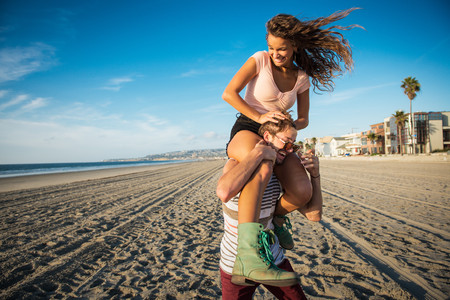 Young man carrying girlfriend on shoulders on San Diego beach LANG_EVOIMAGES