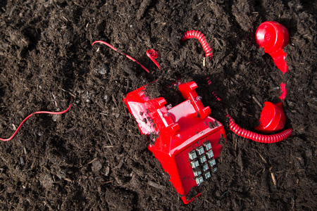 Red retro telephone buried in soil