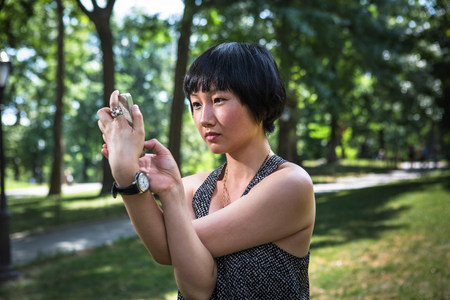 kooky: Young woman holding smartphone with arms twisted LANG_EVOIMAGES