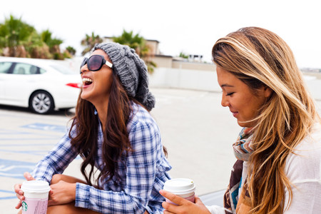 Female friends sitting in car lot,Hermosa Beach,California,USA LANG_EVOIMAGES
