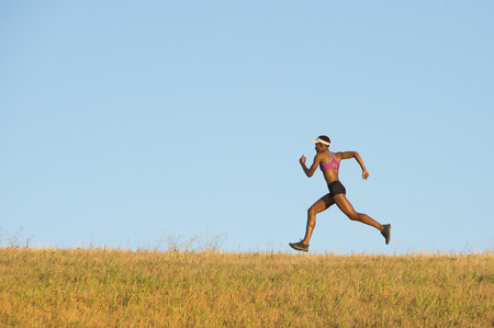 impulsive: Young woman running across field