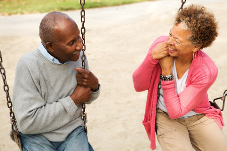 playground rides: Senior couple on swings in park