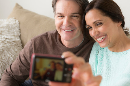 Mature couple photographing themselves with digital camera LANG_EVOIMAGES