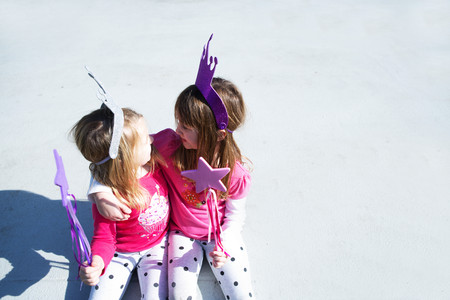 new age: Two young sisters dressed up as fairies holding wands