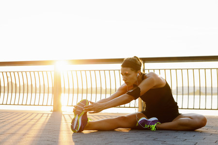entertaining area: Young female jogger stretching at sunrise LANG_EVOIMAGES