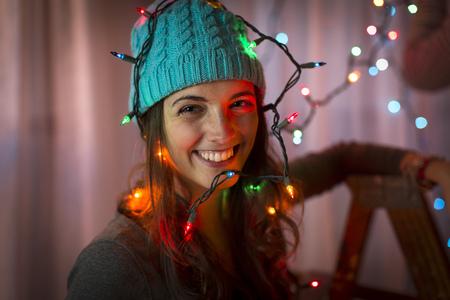 Retrato de mujer joven envuelta en luces de Navidad