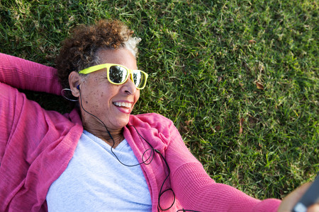 Portrait of senior woman lying on grass wearing sunglasses LANG_EVOIMAGES