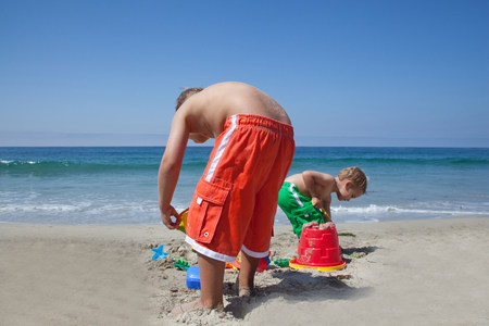 Two young brothers building sandcastles on beach LANG_EVOIMAGES