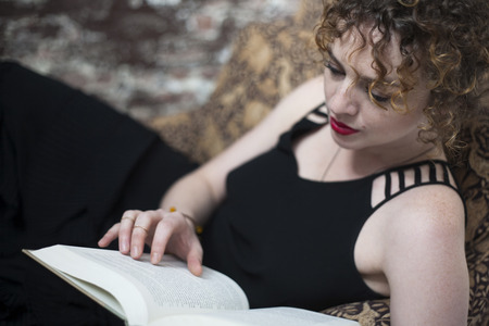 Portrait of young woman reclining and reading book LANG_EVOIMAGES