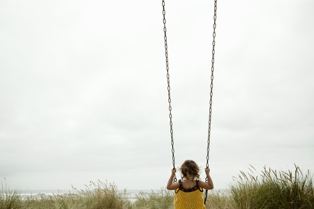 playground rides: Female toddler on beach swing LANG_EVOIMAGES