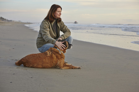 agachado: Mature woman petting her dog on beach LANG_EVOIMAGES