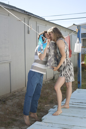 Couple kissing over washing line,Breezy Point,Queens,New York,USA