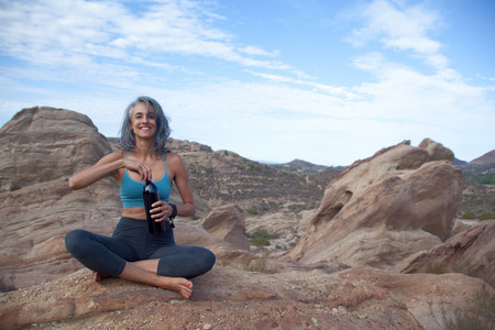 Woman sitting at Vazquez Rocks,opening drinks bottle