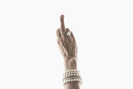 irrespeto: Foto estudio de mano de mujer madura haciendo gesto obsceno LANG_EVOIMAGES