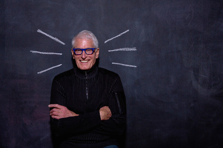 top animated: Portrait of senior man in front of chalked lines on blackboard