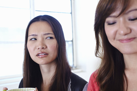 disillusioned: Two young women in kitchen in disagreement LANG_EVOIMAGES