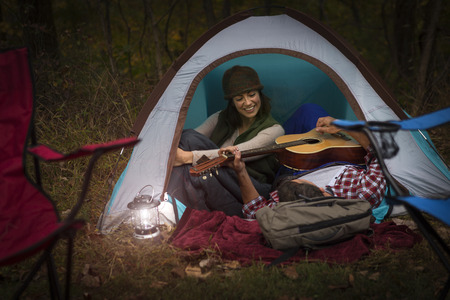 chillout: Mature couple sitting in tent,playing guitar