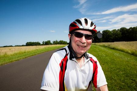 Senior man riding bicycle through countryside LANG_EVOIMAGES