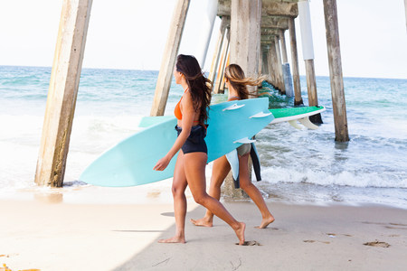 Female friends on beach with surf boards,Hermosa Beach,California,USA LANG_EVOIMAGES