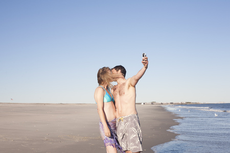 Couple taking self portrait on beach,Breezy Point,Queens,New York,USA