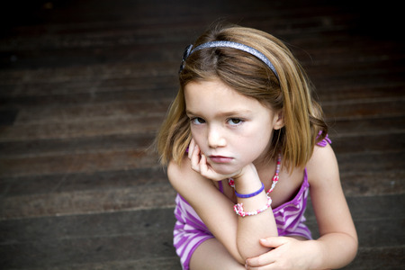 squabble: Sullen young girl sitting on porch with hands on chin LANG_EVOIMAGES