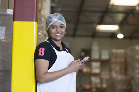 Portrait of female factory worker using cell phone