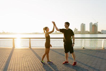 mornings: Jogging couple celebrating on riverside early morning