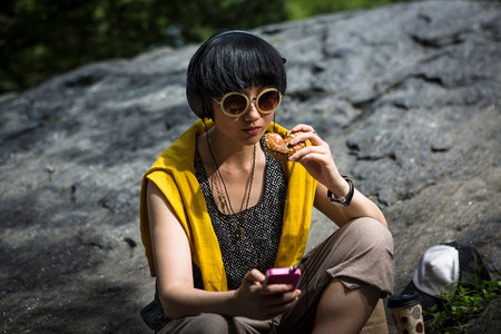 Young woman eating snack with mp3 player