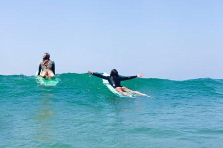 Female friends surfing,Hermosa Beach,California,USA