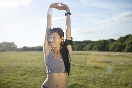 armbands: Young female runner stretching arms and warming up LANG_EVOIMAGES